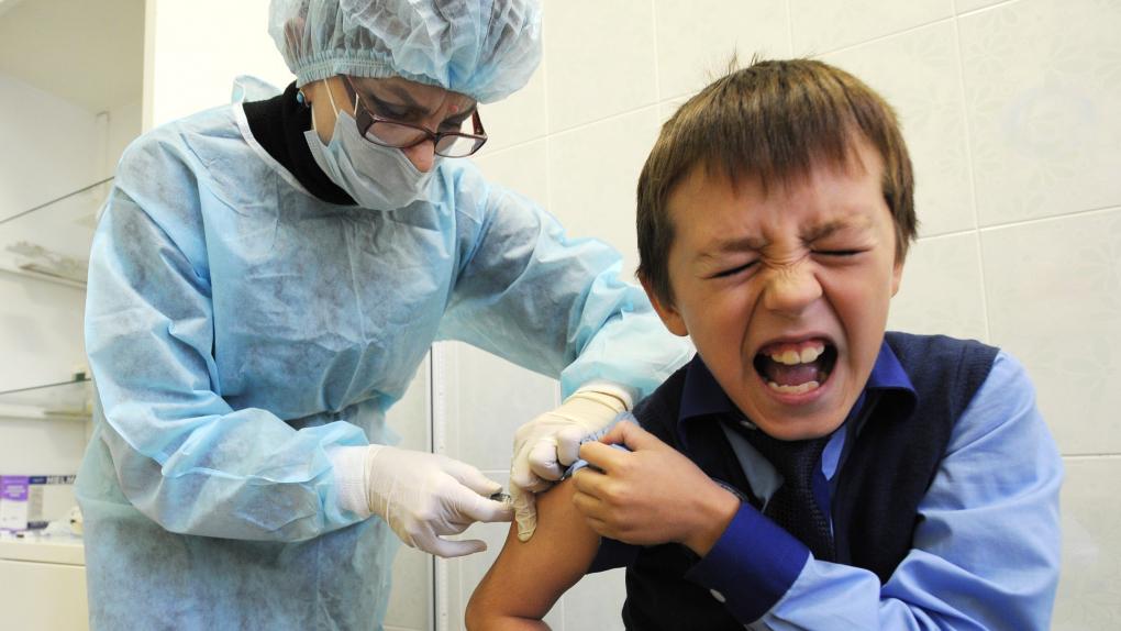 Детский врач делает школьнику прививку против гриппа во время профилактического медицинского осмотра