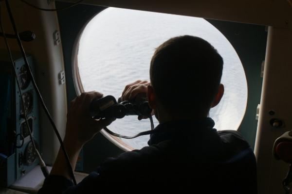 Сотрудник МЧС России в самолете Бе-200 во время обследования акватории Охотского моря