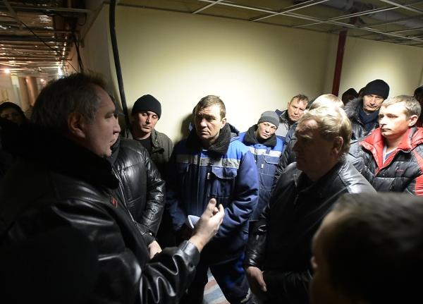 Вице-премьер РФ Дмитрий Рогозин (слева) общается со строителями во время визита на космодром Восточный