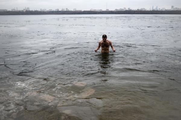 Мужчина купается в Строгинском заливе в Москве 21.12.2015