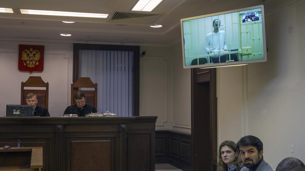 Юсуп Темирханов (на экране), осужденный за убийство бывшего командира 160-го гвардейского танкового полка Юрия Буданова, и его адвокат Мурад Мусаев (справа) во время рассморения жалобы на приговор в Верховном суде РФ